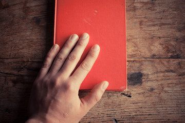 Hand on a red book