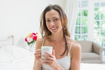Relaxed young woman with coffee cup in bed