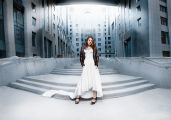 woman in white dress standing on stairs against modern building