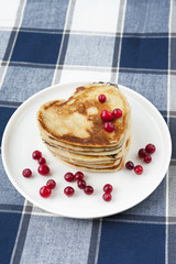 Heart shaped pancakes with cranberries on porcelain plate. Close