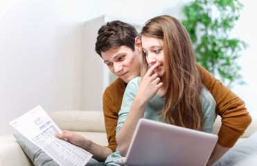Young anxious couple consults their bank account