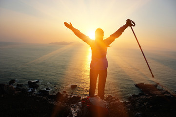 cheering woman hiker open arms at sunrise seaside