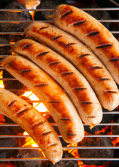 Sausages cooking on a barbecue fire
