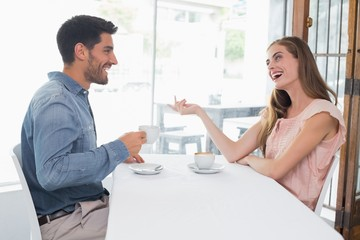 Side view of a smiling couple at coffee shop