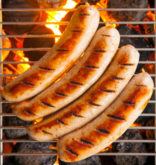 Four sausages called bratwurst, grilling over hot coals on a BBQ