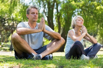 Couple meditating in park