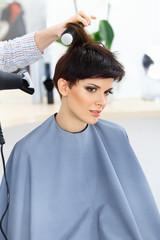 Hairdresser Using Dryer on Woman Wet Hair.