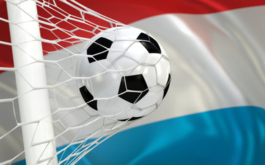 Flag of Luxembourg and soccer ball in goal net