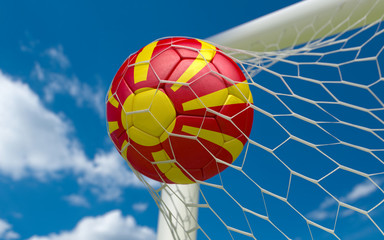 Flag of Macedonia and soccer ball in goal net