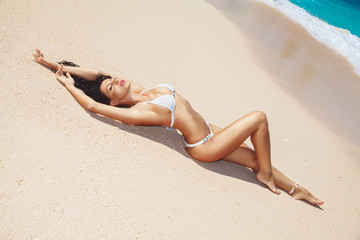 young woman is  laying at the tropical beach