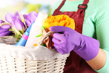 Housewife holding basket with cleaning equipment
