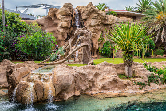 Big animal enclosure in a zoo with a waterfall