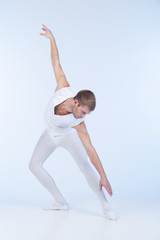 young ballet dancer practicing in white.