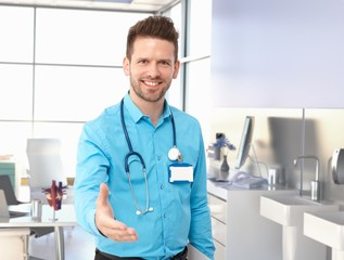 Smiling doctor offering hand in exam room
