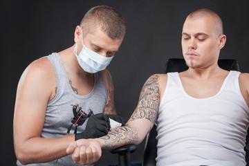 professional tattooist doing tattoo on hand.