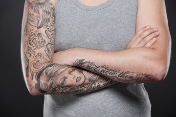 folded tattooed hands of young guy.