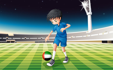 A boy kicking the ball with the United Arab Emirates flag