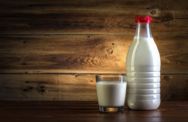 glass and bottle of milk on wooden background