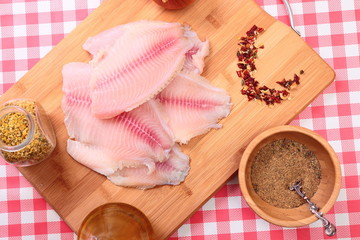 Raw fish tilapia on cutting board and spices
