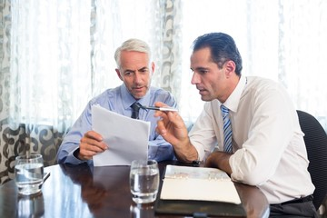 Businessmen doing paperwork at office desk
