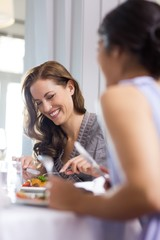 Smiling woman having food with friend at restaurant