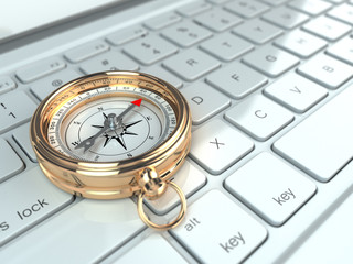 Online navigation. Compass on laptop keyboard.