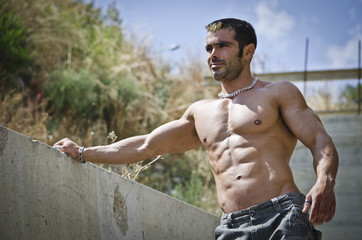 Muscle man shirtless outdoors leaning against concrete wall