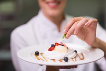 Happy chef putting mint leaf on dessert plate