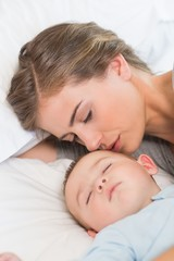 Mother sleeping with baby boy on bed