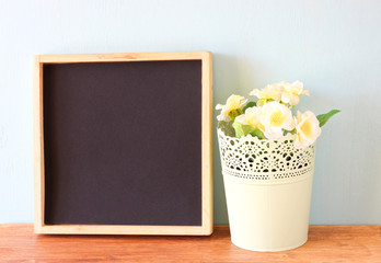 empty blackboard and flowerpot over wooden shelf