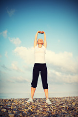 Fototapete - woman in white doing yoga and sport exercises on  beach