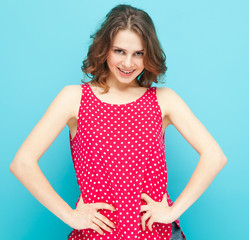beautiful girl in a red blouse with polka dots on a blue backgro