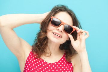 beautiful girl in sunglasses on a blue background in soft focus