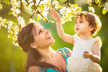 Happy woman and child in the blooming spring garden.