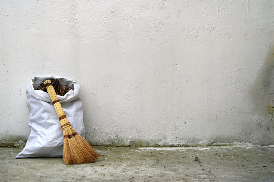 Textural background. Bag of garbage and broom against wall