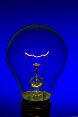 Glass light bulb with burning filament upright with blue backgro