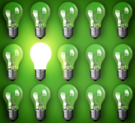 Idea concept with light bulbs on green background