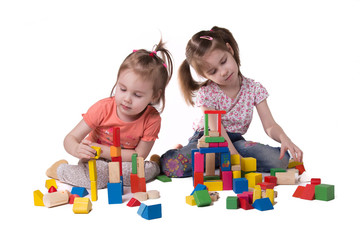 two girls playing with colorful wooden designer sitting