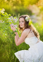 Wall Mural - Beautiful spring girl with flowers on the meadow