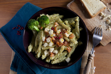 Pasta broccoli salmon pink peppercorns and crumble bread on bowl