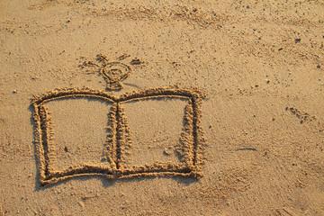 Book and light bulb drawn on sand beach
