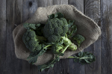 raw broccoli on gunny sack on rustic wooden table