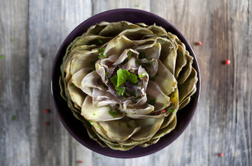 artichoke like lotus flower with parsley and peppercorns on bowl