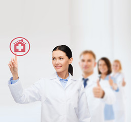 smiling female doctor pointing to hospital sign