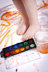 Close-up of small child's legs and watercolors