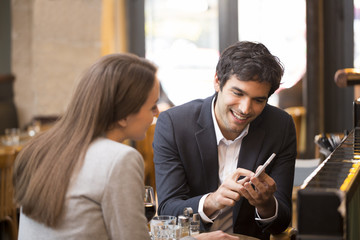 In a restaurant cheerful couple surfing the web on smartphone