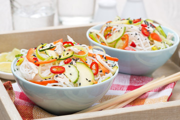 Thai salad with vegetables and chicken in a bowls