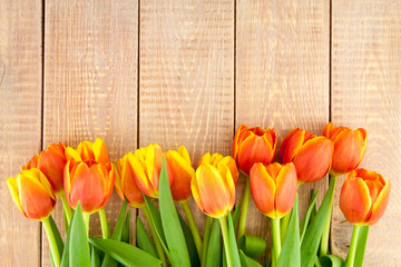 bouquet of yellow and orange tulips on a wooden background