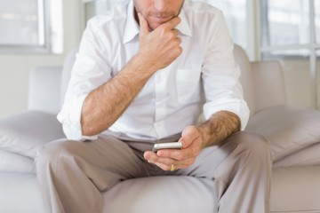 Mid section of man text messaging at home