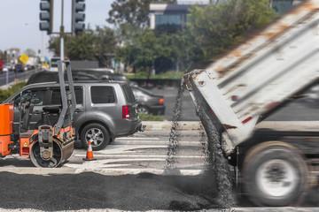 Road paving repairs on suburban city street.Dump truck,asphalt.